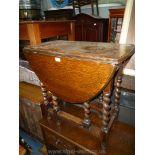 A dark Oak drop-leaf gateleg Table standing on twist supports, 30 1/4'' x 14'' extending to 41'',