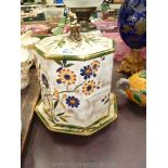 An octagonal cheese dish decorated with yellow and blue flowers with gold finial,