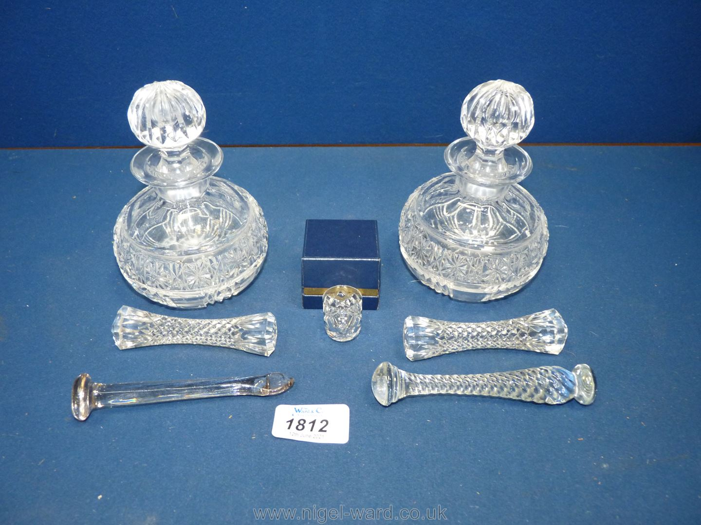 Two glass dressing table bottles with stoppers, one a/f., glass knife rests and a glass thimble.