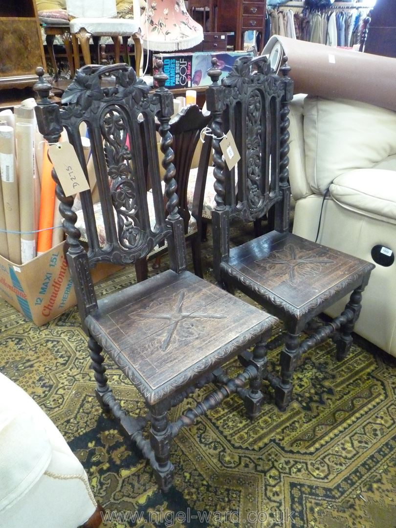 A pair of dark Oak hall/Side Chairs of early design with carved solid seats, twist legs,