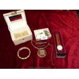 A cream jewellery box containing loose pearls, brooches, ring, tie pins,