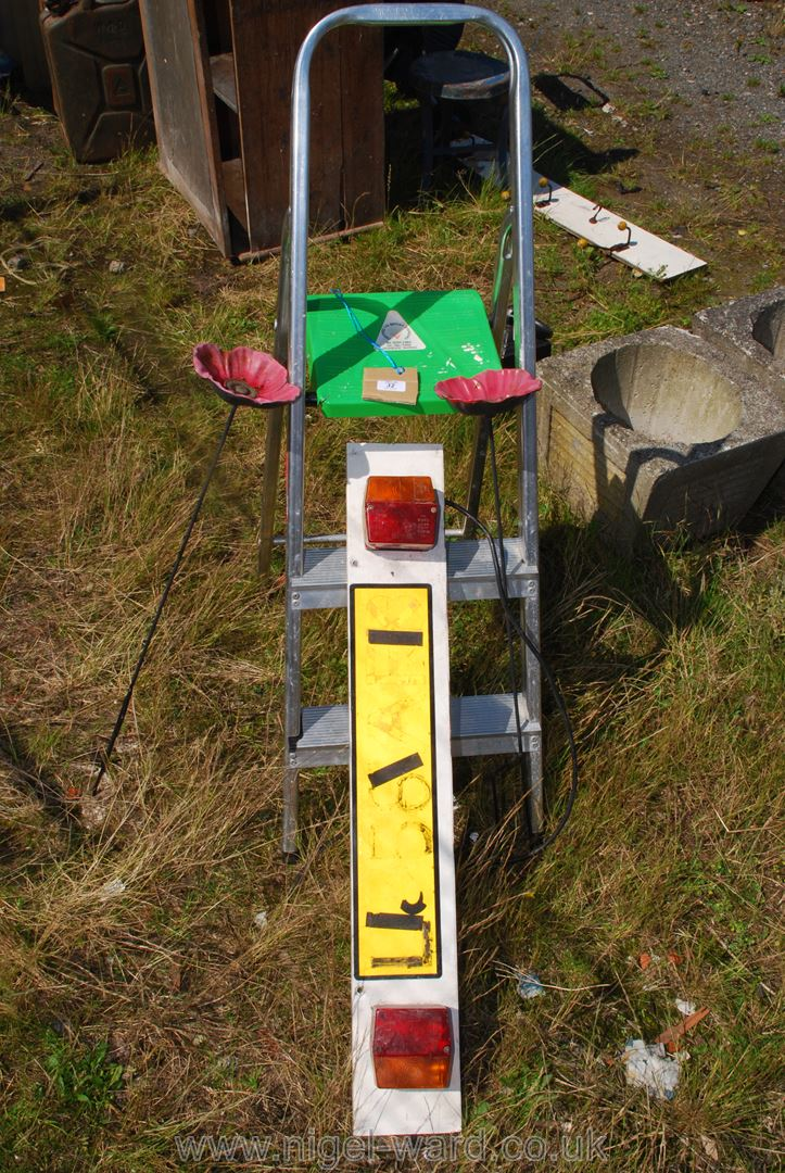 Trailer board, two metal garden poppies and a small stepladder.