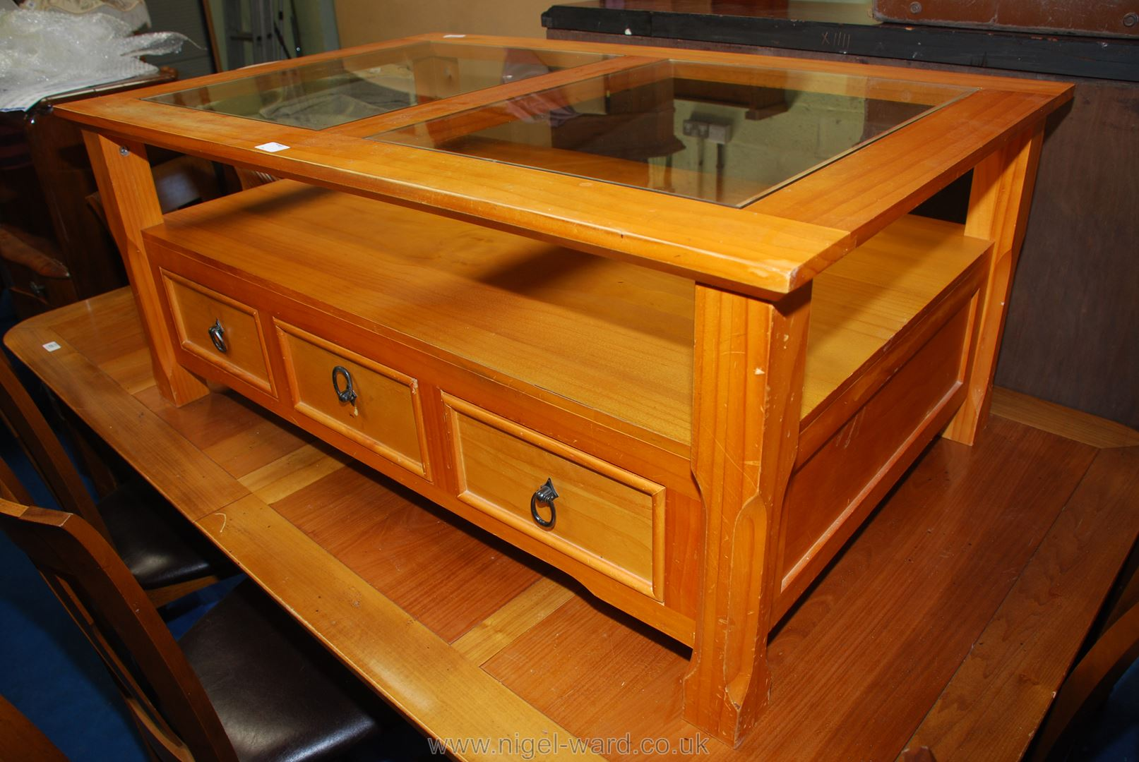 A glass topped coffee table with three drawers