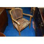 Cane backed low oak armchair