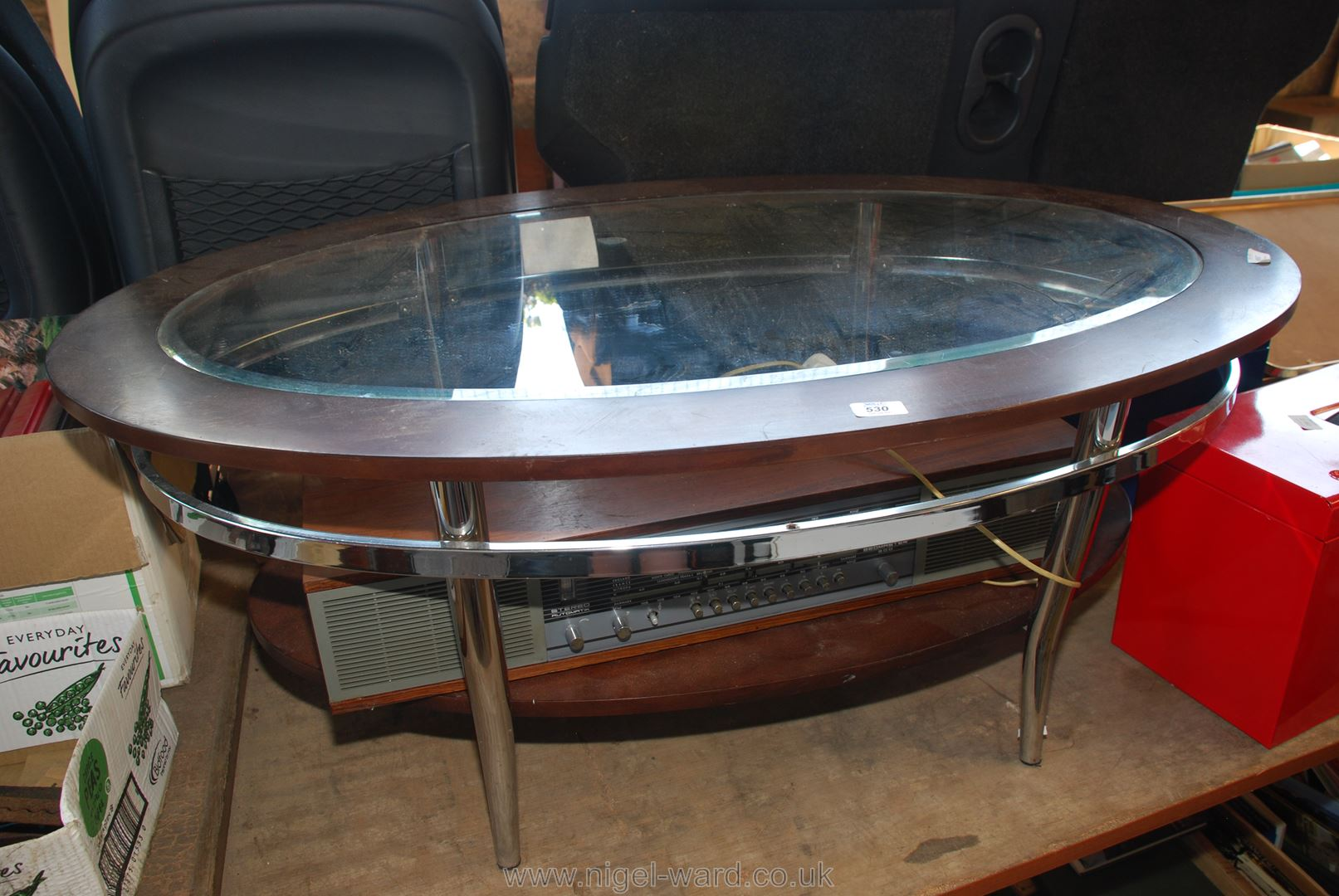 An oval glass topped coffee table.