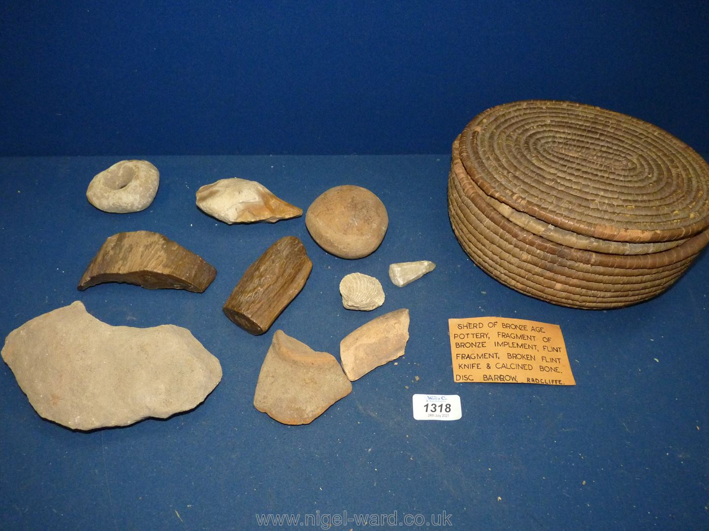 An antique woven reed lidded basket containing a collection of; fossils, petrified wood,