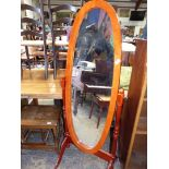 A contemporary honey coloured Mahogany oval Cheval/Robing Mirror having turned supports,