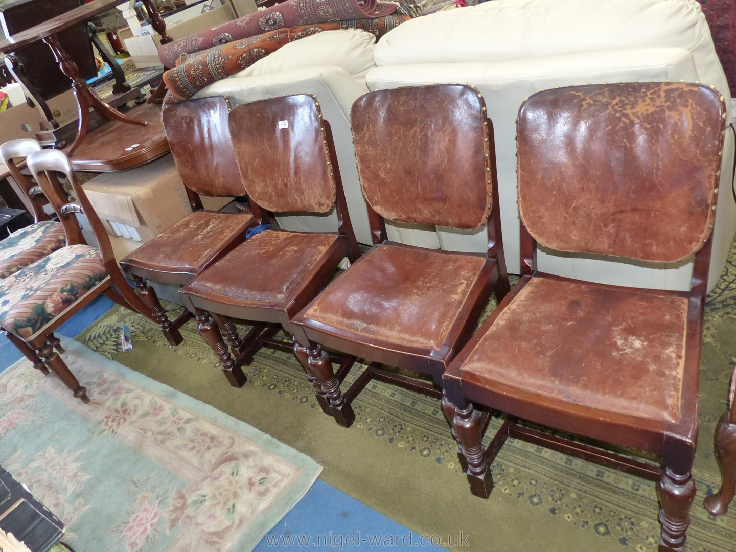 A set of four Oak framed Dining Chairs having brown hide upholstered backs and drop-in seats.