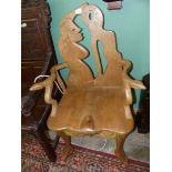 A unique contemporary mixed hardwoods elbow chair having splayed arms terminating in carved animal