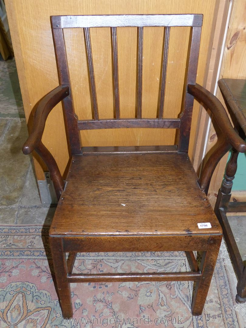A Georgian Oak solid seated Elbow Chair having back rest with four triple reeded uprights.