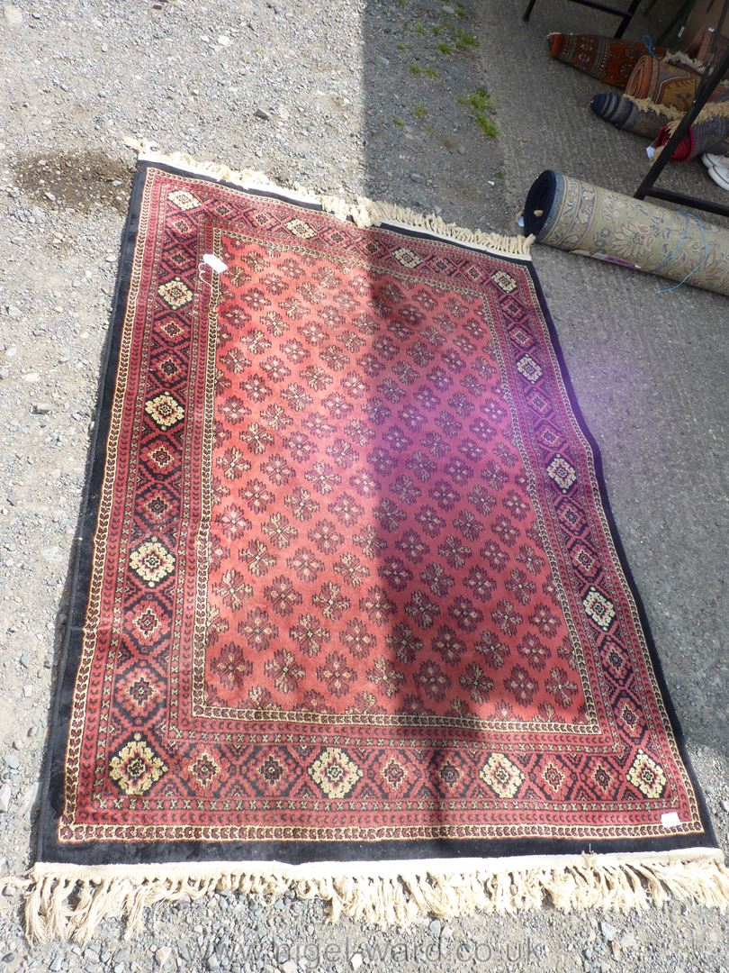 A bordered, patterned and fringed Rug,
