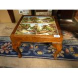 """A small tiled top table/stand, the tiles having farming scenes, 11"""" tall x 14 1/2"""" wide."""