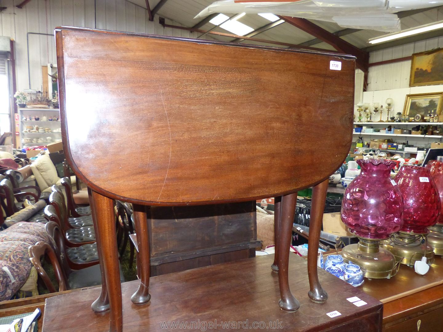 A good Mahogany drop-leaf swing-leg Dining Table standing on cabriole legs terminating in pad feet,