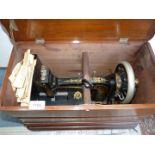 A Bradbury Hand Sewing Machine in wooden case.