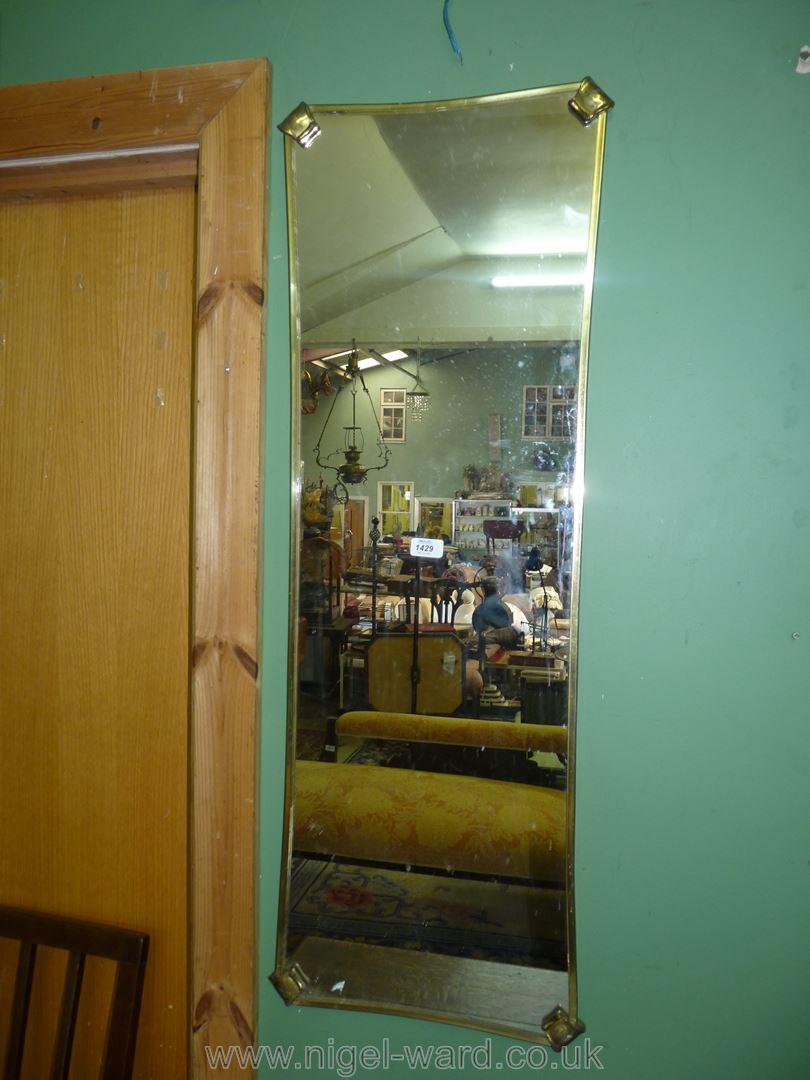 A shaped metallised framed wall mirror, 45 3/4'' x 16''.