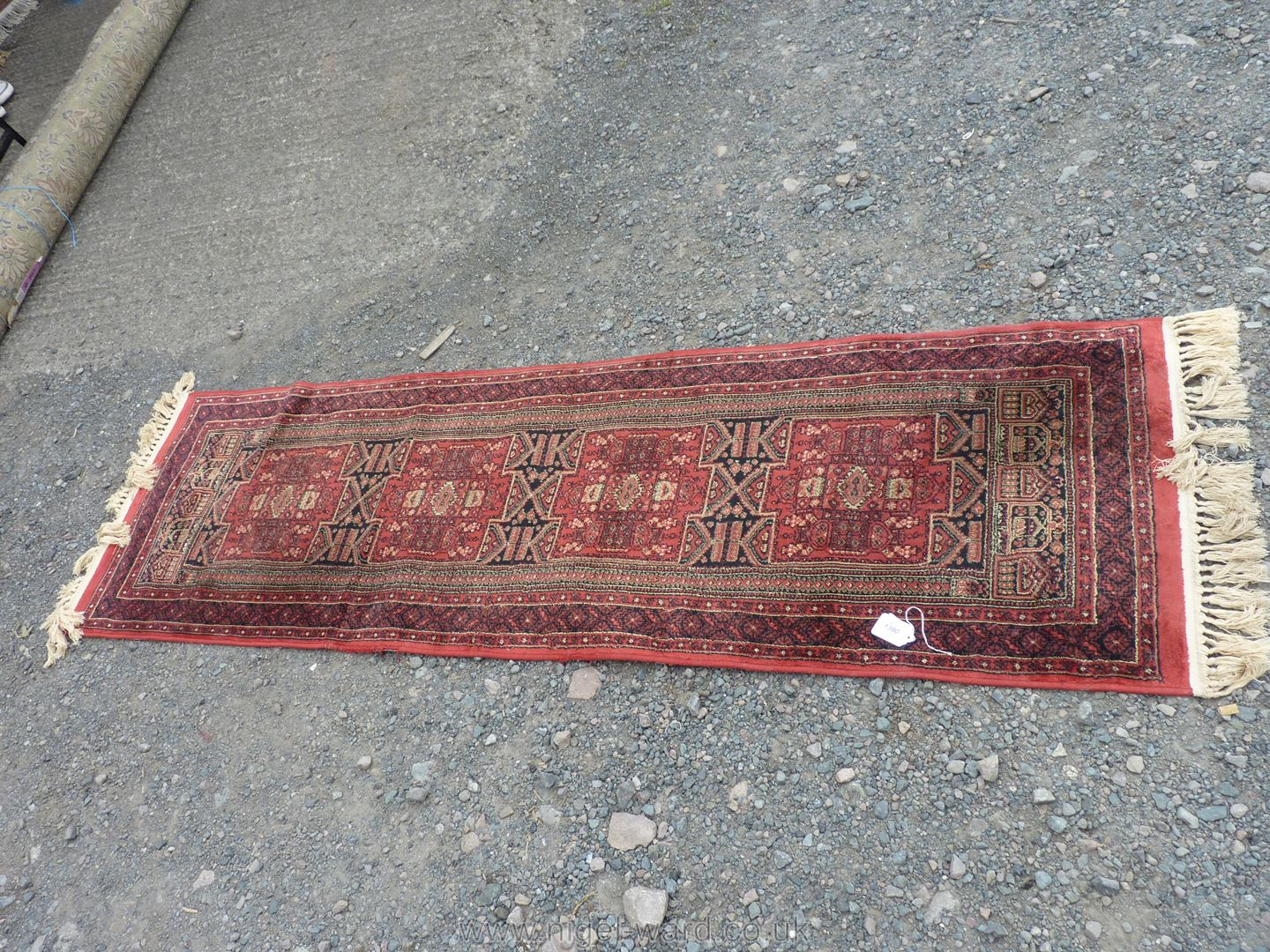 A Belgian Runner, burgundy ground with geometric pattern, 82'' long x 25'' wide.