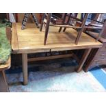 A light Oak drawleaf Dining Table standing on moulded detail square legs,