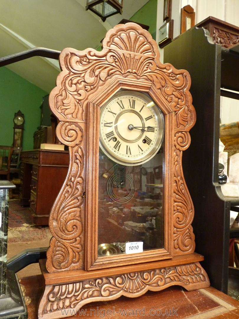 A mantle clock carved surround having floral motif and scrolling, complete with key and pendulum,