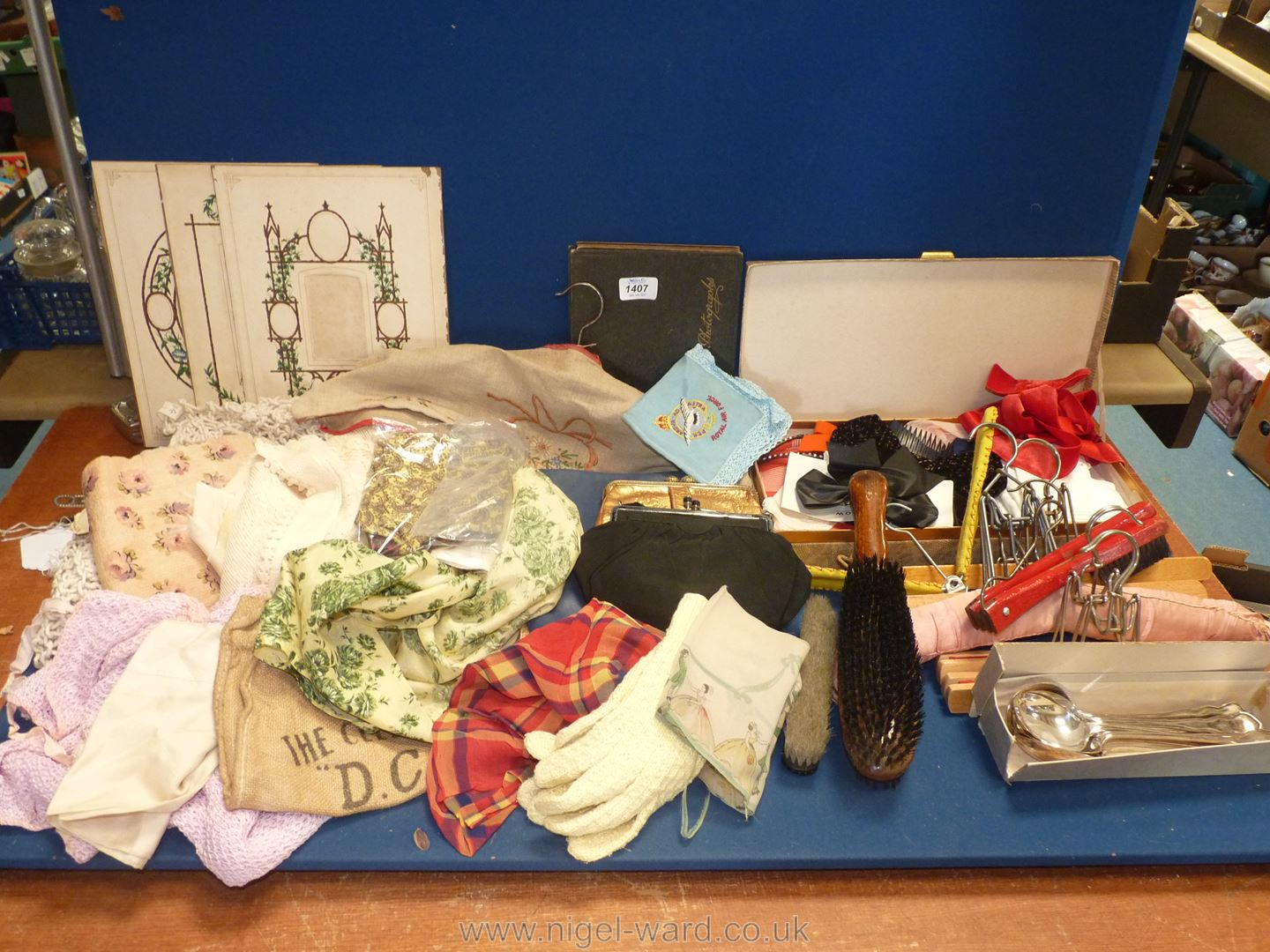A box of miscellanea to include; hair bows, clothes brushes, hangers, linen & crochet items,