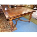 A Mahogany and Walnut draw leaf Dining Table standing on turned and tapering eight sided legs with