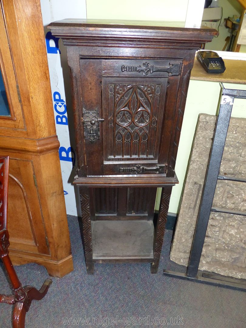 A most appealing carved dark Oak Cabinet on stand,