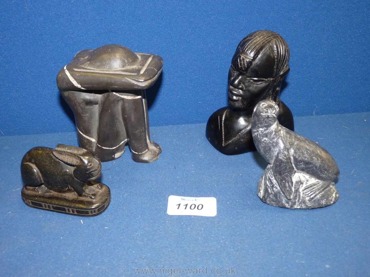 Four carved stone figures including seal, female bust, hare, etc.