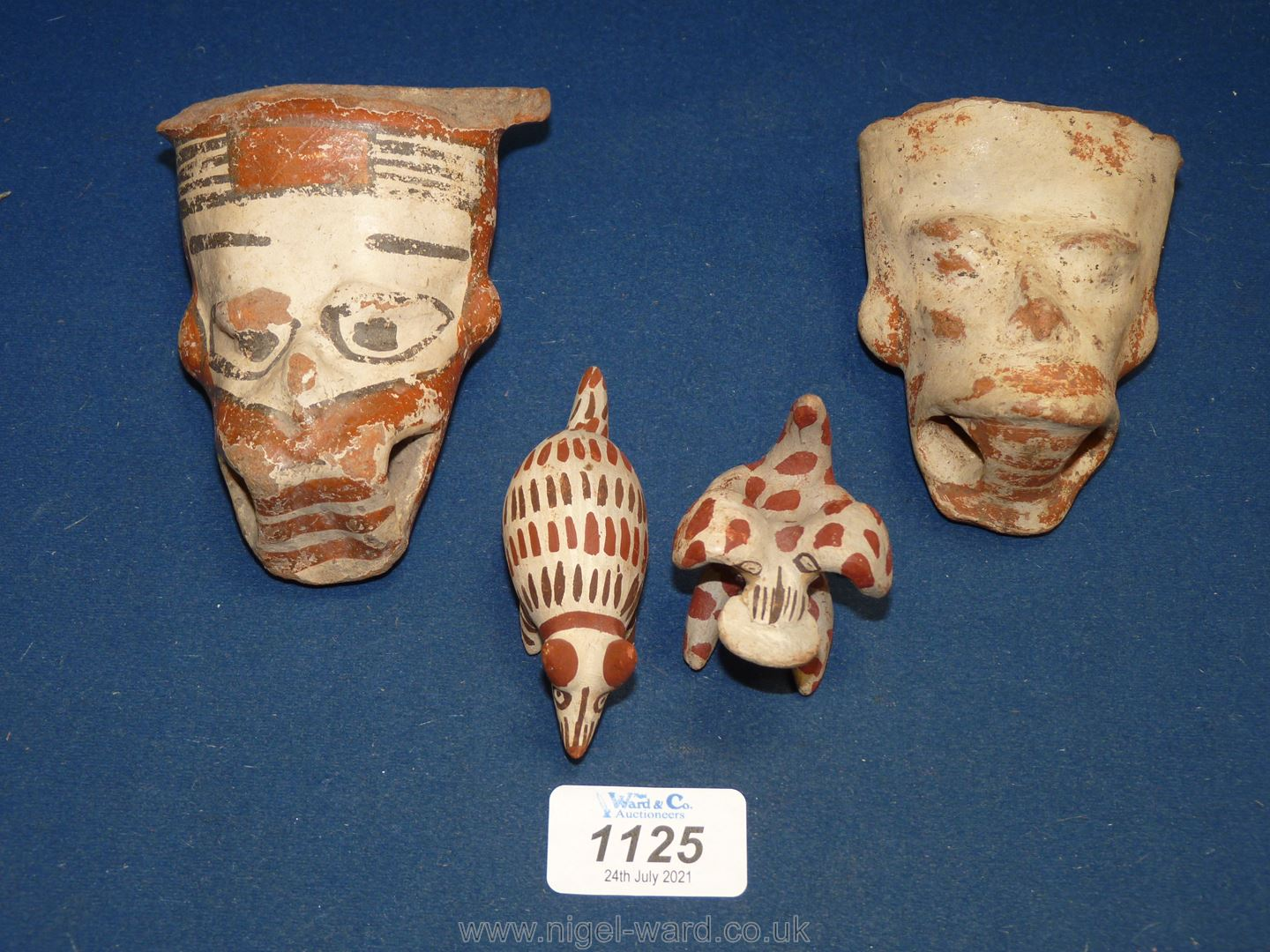 Two pottery heads with rattle balls inside and two small animals.
