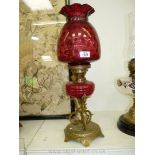 An oil Lamp with an ornate brass base, red glass ribbed reservoir, double wick burner,