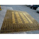 A large bordered, patterned and fringed Rug, gold ground with black geometric pattern,