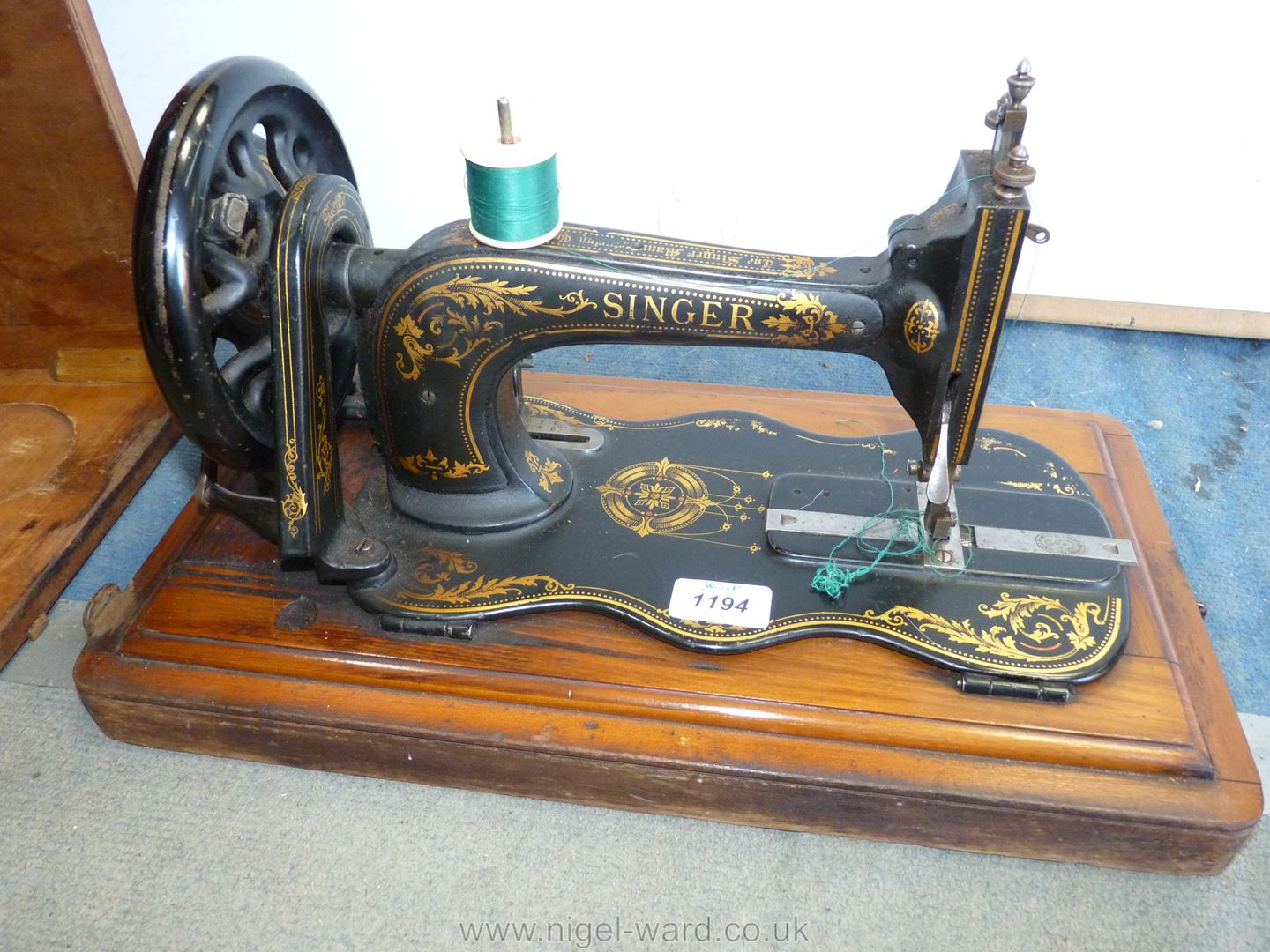 A Singer Hand Sewing Machine in wooden case.