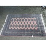 A modern wool Bakhara Rug, main colour pink with lozenges on the central panel, 4'8'' x 6'.