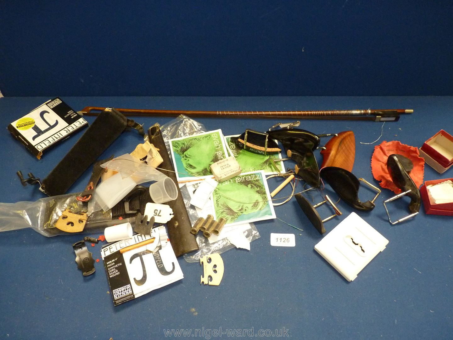A box of violin components including rests, strings, resin, bow etc.