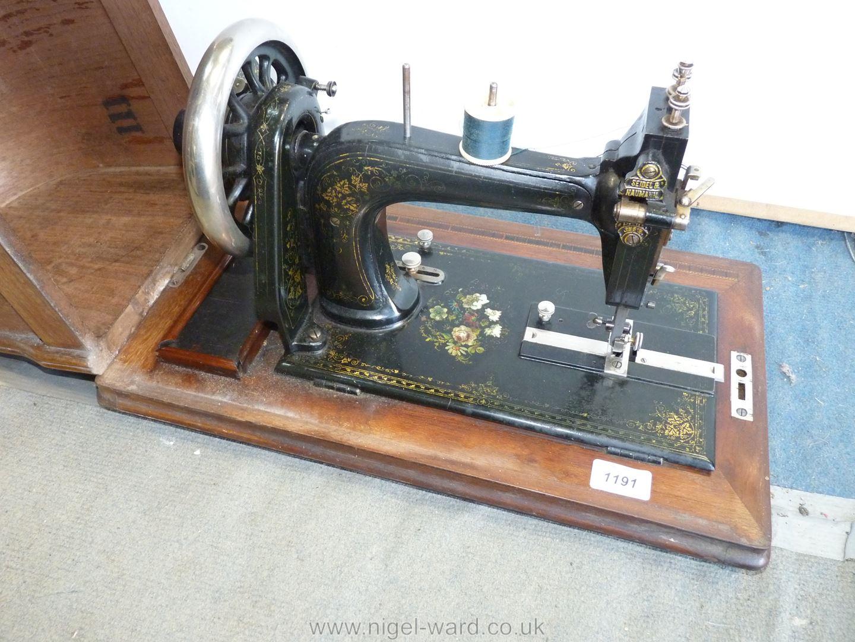 A Naumann Hand Sewing Machine in wooden case.