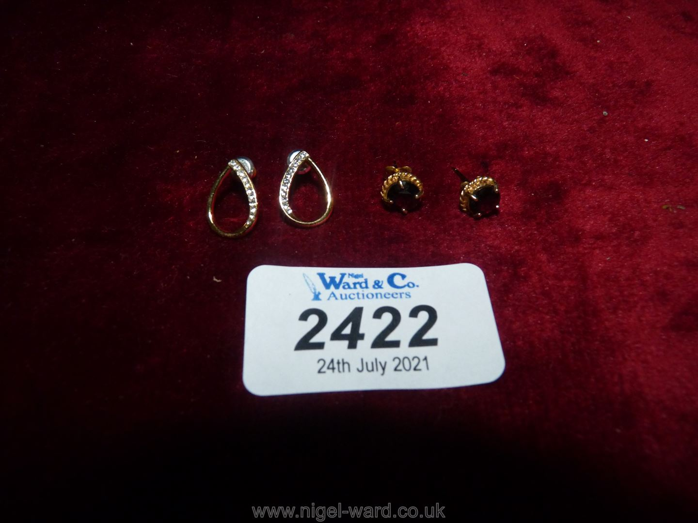 Two pairs of yellow metal ear-rings one set with red stone the other with white chips.