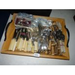 A large quantity of cutlery on a wooden tray including fish knives, forks and servers etc.