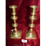 A pair of brass candlesticks with pushers.