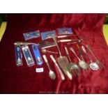 A quantity of plated items including cheese markers, berry spoon, pickle and bread forks,