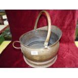 A vintage brass coal bucket.