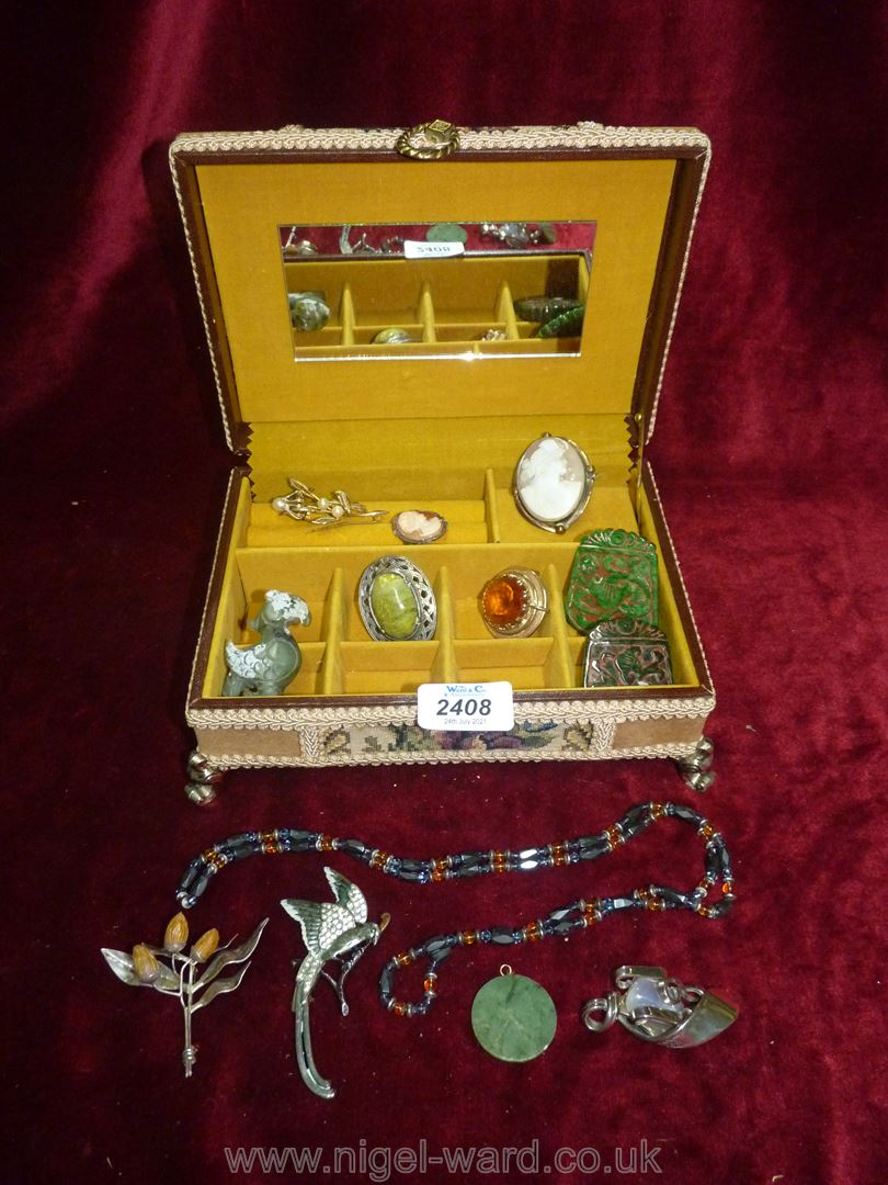 A fabric covered musical jewellery box and contents including brooches, cameos,