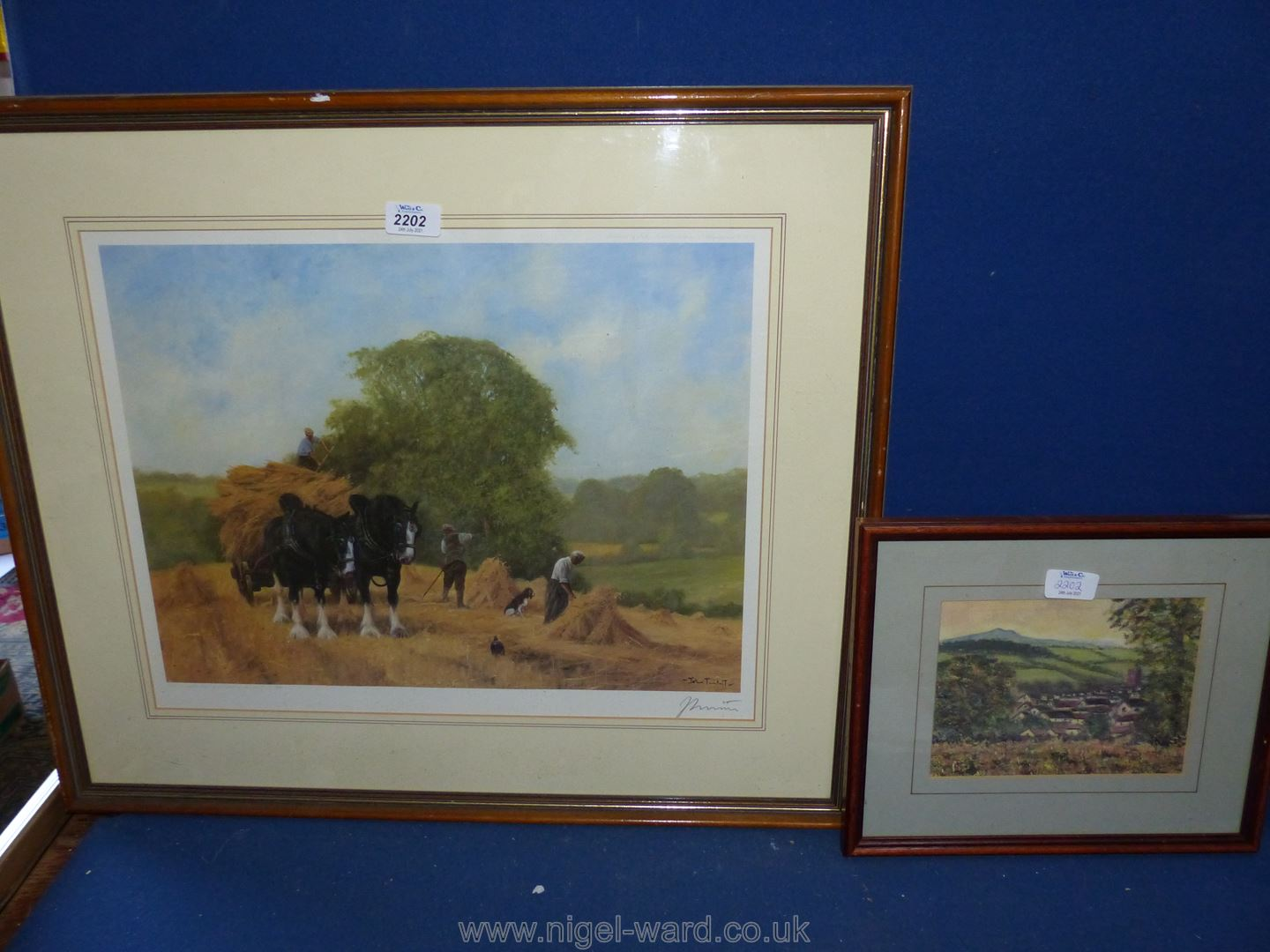 A small framed print of a village countryside scene indistinctly signed,