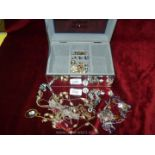 A mirrored box of costume jewellery ear-rings, owl pendant etc.