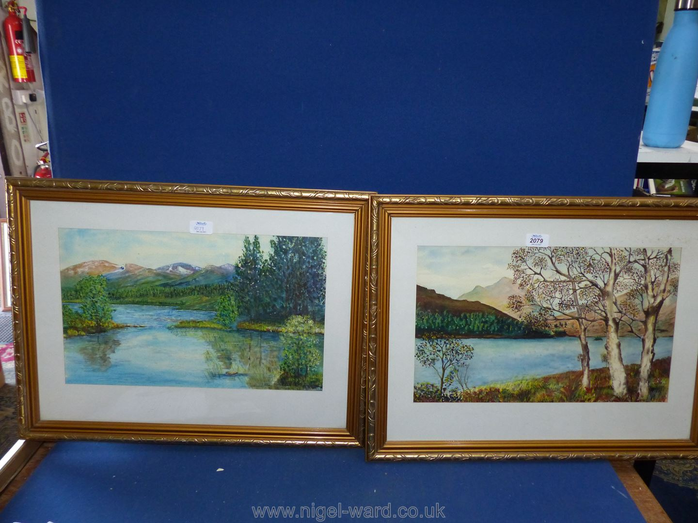 A pair of gilt framed watercolours depicting river landscapes and hills in the distance,