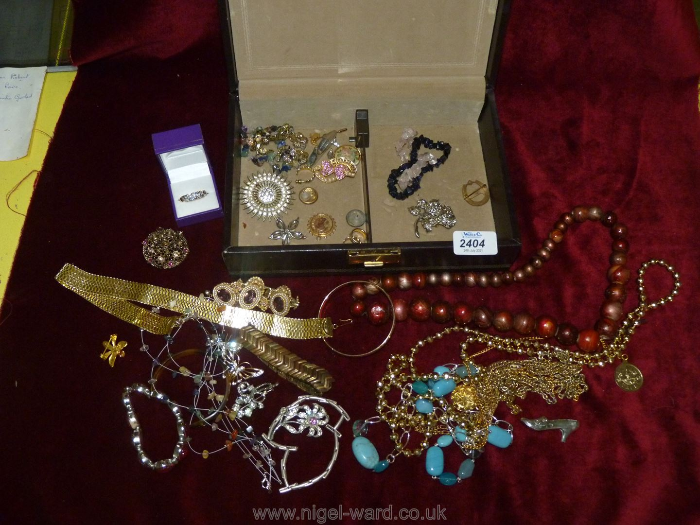 A Jewellery box and contents including brooches, beads,