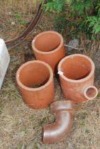 "Three terracotta chimney stoves, 10"" diameter and a salt glazed drainage bend."