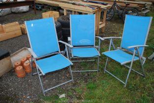 Three nylon and metal folding chairs.