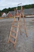 A five rung wooden set of stepladders.