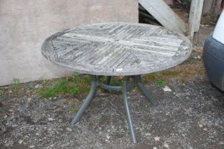 """A wooden patio table, 47"""" diameter."""