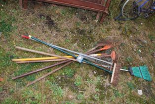 A quantity of garden rakes and brooms.