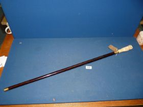An ebonised vintage walking stick surmounted with a well carved bone owl knop and brass fittings.