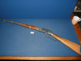 A heavy replica 1886 Winchester under-lever rifle with cocking and firing action.